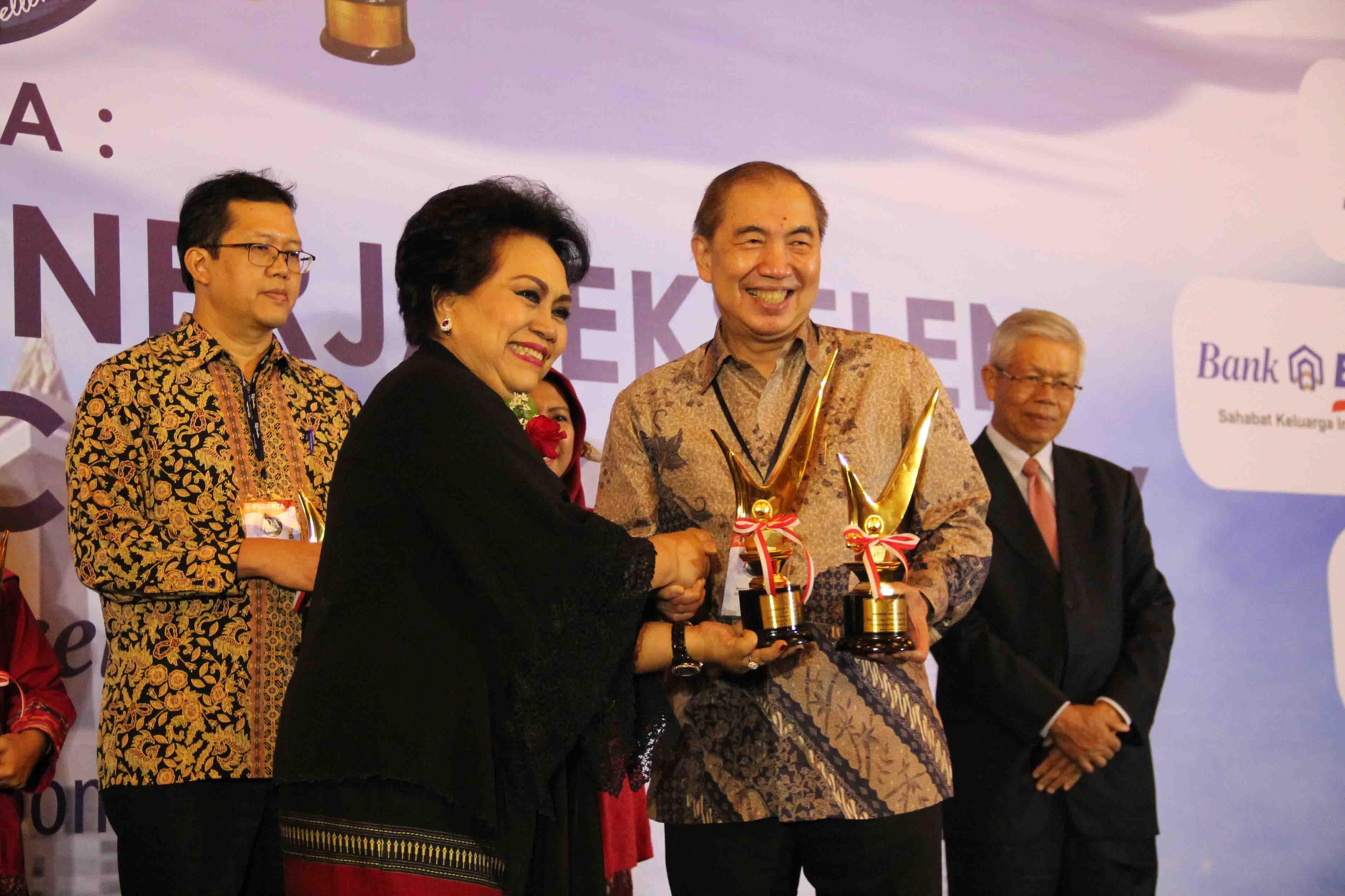 Penyerahan Piala oleh Ibu dr. Orie Andari Sutadji, MBA (IQAF) kepada Bapak Ir. Bernard Gunawan (CEO Bina Nusantara)